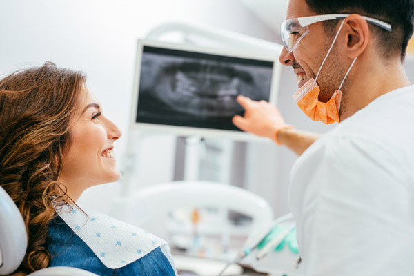Dentist explaining an xray to a woman patient at Malmquist Oral and Maxillofacial Surgery in Portland, OR