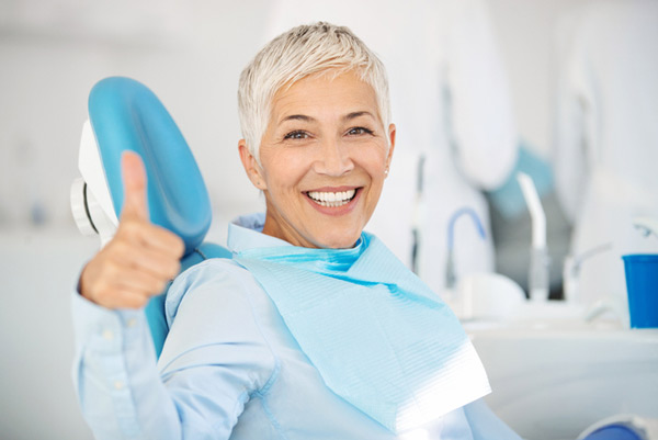 Mature woman smiling in a dental chair showing a thumbs up before getting dental implants at Malmquist Oral and Maxillofacial Surgery