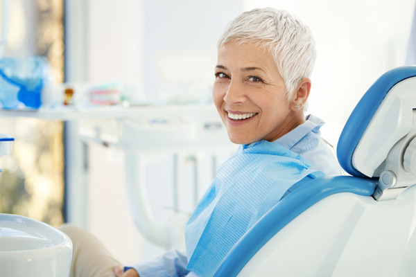 Woman smiling in dental chair before getting teeth in an hour at Malmquist Oral and Maxillofacial Surgery